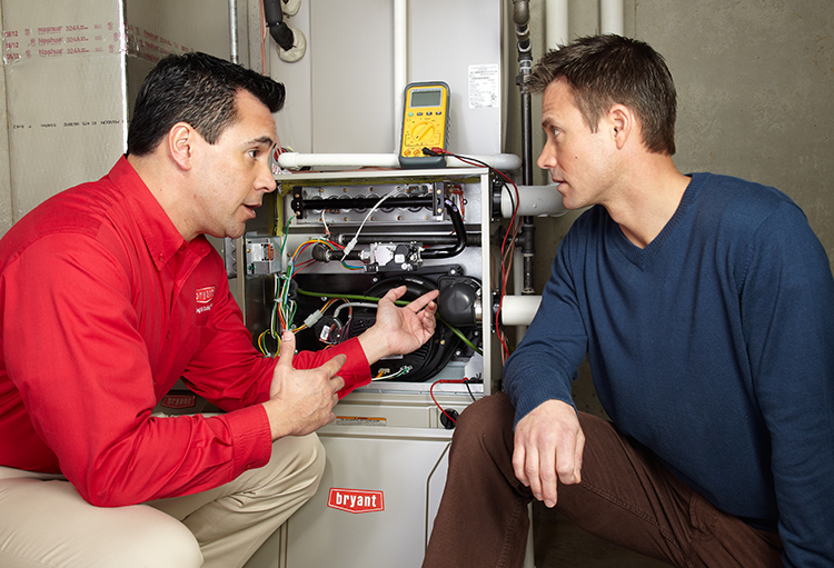 Bryant Heating and Cooling HVAC tech with homeowner explaining furnace repair
